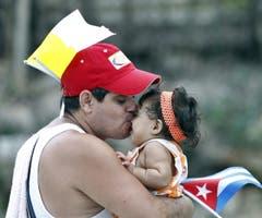 Küssend wartet dieser Vater mit seiner Tochter am Strassenrand auf den Papst. (Bild: Keystone)