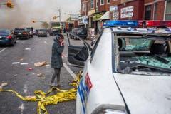 Ein Mädchen beschaut sich ein demoliertes Polizeiauto. (Bild: Keystone/EPA/Noah Scialom)