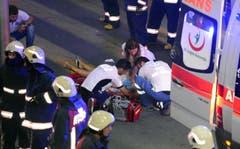 Helfer vom türkischen Rettungsdienst versorgen Verletzte ausserhalb des Flughafen in Istanbul. (Bild: Ismail Coskun)