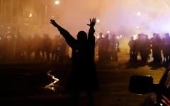 Vor dem Polizeikordon macht sich ein Demonstrant davon. (Bild: AP Photo / David Goldman)