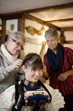 Silvia Käslin, links, zieht Silvia Gut den Kopfschmuck an (Bild: Corinne Glanzmann / Neue NZ)
