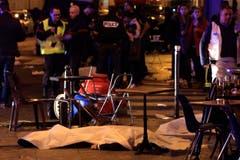 Vor einem Cafe in Paris liegen zwei Todesopfer des Terroranschlags. (Bild: AP/Thibault Camus)