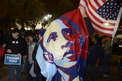 Ein Mann schwenkt vor dem Weissen Haus in Washington eine Obama-Fahne. (Bild: Keystone)