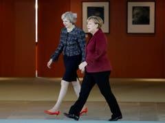 Angela Merkel, eher bescheiden mit schwarzen Halbschuhen, neben Theresa May in rotem Lack. (Bild: Michael Sohn/AP)