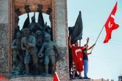 Menschen zeigen die türkische Flagge und protestieren am Samstag gegen den Militärputsch auf dem Taksim Platz in Istanbul. (Bild: AP Photo/Emrah Gurel)