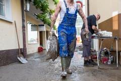 Ein Mann beim Aufräumen in Pfäffikon (Bild: Keystone / Alexandra Wey)