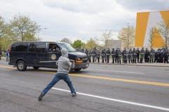 Ein Demonstrant schleudert einen Stab gegen ein Fahrzeug. (Bild: EPA/ Michael Reynolds)