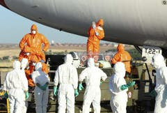 Ärzte und Hilfskräfte verladen den spanischen Priester Miguel Pajares, der sich bei der Arbeit in Liberia mit dem tödlichen Virus infizierte,von einem Flugzeug zu einer Ambulanz. (Bild: Keystone)
