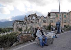 Bewohner von Amatrice vor eingestürzten Gebäuden. (Bild: AP / Alessandra Tarantino)