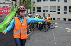 Instruktorin Flavia Zimmermann zeigt den Kindern, wie die Armzeichen vor dem Abbiegen sind. (Bild: Markus von Rotz (Neue NZ))