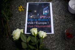 Mit einem Poster und Blumen wird vor der französischen Botschaft in Berlin der Opfer gedacht. (Bild: AP/Markus Schreiber)