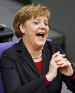 Die deutsche Bundeskanzlerin Angela Merkel hat auch manchmal Grund zum Lachen - sogar während einer Sitzung im Bundestag, am 16. März 2006. (Bild: Keystone)