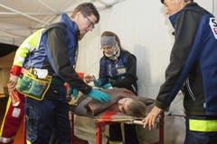 Eine verletzte Frau liegt auf der Rettungsliege und der Notarzt versorgt sie. (Bild: Edi Ettlin)