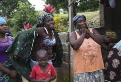 Liberianische Angehörige trauern um einen Verwandten, der an Ebola gestorben ist und gerade weggetragen wird. (Bild: Keystone)
