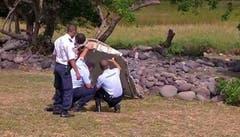Französische Polizisten untersuchen das gefundene Wrackteil. (Bild: Keystone)