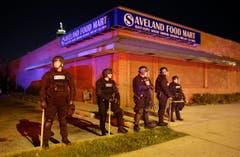 Polizisten stehen vor einem Geschäft. (Bild: AP Photo/Patrick Semansky)