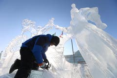 Ebenfalls in der Ferne: In der Eis- und Schneewelt in Harbin in Nordchina bearbeitet ein Künstler das gefrorene Material seines Werks. (Bild: EPA/WU HONG)