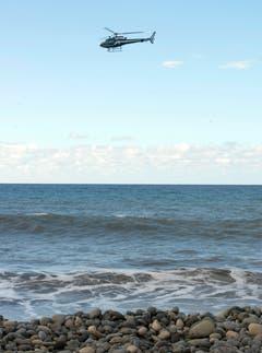 Ein Helikopter bei der Suche weiterer Hinweise über dem Strand von La Réunion. (Bild: Keystone)
