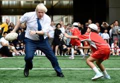 Boris Johnson weicht einem Kind aus. (Bild: AP / Stefan Rousseau)