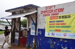 Ein liberischer Soldat bewacht den Kontrollpunkt, damit keine Menschen in die von Ebola befallene liberische Hauptstadt gelangen und sich das Virus damit noch weiter verbreitet. (Bild: Keystone)