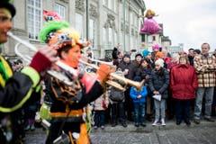 """Zuschauer beobachten kostümierte Personen die Trompete spielen und am Umzug """"ZüriCarneval 2015"""" teilnehmen. (Bild: ENNIO LEANZA)"""