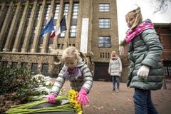 Kinder legen vor der französischen Botschaft in Den Haag Blumen nieder. (Bild: EPA/Alexander Schippers)