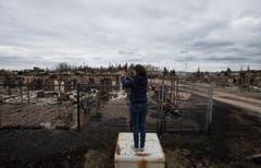 Eine Reporterin macht sich Bilder von der Zerstörung. (Bild: Ryan Remiorz/The Canadian Press via AP)