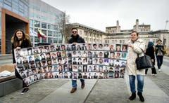 Vor dem Gericht in Den Haag verleihen Aktivisten der Forderung nach einer Verurteilung Nachdruck: Sie zeigen Bilder von Opfern des Krieges. (Bild: EPA/KOEN VAN WEEL)