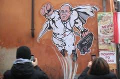 Ein auf einer Hausmauer in Rom angebrachter Wandsticker zeigt Papst Franziskus als Superhelden und ist bei Passanten ein beliebtes Fotomotiv. (Bild: Keystone)