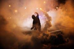Ein Protestierender wirft eine rauchende Petarde zurück. (Bild: AP Photo / David Goldman)
