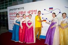 Dieses Bild zeigt den Fotografen Martin von den Diresch. Hinter ihm und den nordkoreanischen Frauen hängt die Karte mit der Route, die er mit seinem Team während sechs Wochen in Nordkorea zurückgelegt hat – fast 17 000 Kilometer! (Bild: Martin von den Driesch)