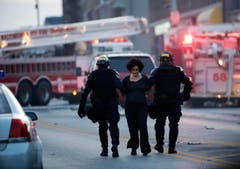 Eine Demonstrantin wird von Polizisten abgeführt. (Bild: AP Photo/Matt Rourke)
