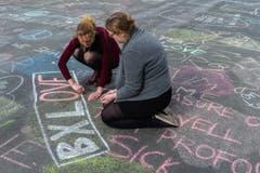 Auf dem Platz vor der Börse in Brüssel schreiben zwei Frauen ihre Botschaft der Solidarität. (Bild: AP Photo / Geert Vanden Wijngaert)