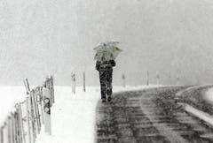 Eine Spaziergängerin mit Schirm geht durch die verschneite Landschaft in Ennetmoos. (Bild: Keystone)