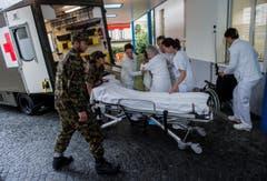 Patienten werden am Dienstag wegen drohendem Hochwassers aus der Clinica Santa Chiara in Locarno evakuiert. (Bild: Keystone)