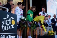 Fahrer der Tour de France legen bei der Siegerehrung Blumen nieder. (Bild: AP / Christophe Ena)