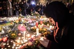 Eine Frau zünden eine Kerze an. (Bild: EPA/CHRISTOPHE PETIT TESSON)