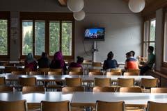Asylsuchende schauen sich Musik Videos im Speisesaal an. (Bild: Dominik Wunderli)