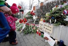 Ein Kind legt vor der französischen Botschaft in Moskau Blumen nieder. (Bild: EPA/Sergei Chrikov)