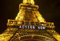 Auch der alte Eiffelturm muss für Slogans hinhalten. (Bild: AP Photo/Michel Euler)