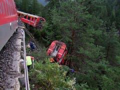 Riesiges Glück hatte die Bahnreisenden im ersten Wagen nach der Lokomotive. Gemäss Angaben eines Passagiers stürzte dieser Wagen etwa 20 Meter vom Trassee und blieb im Steilhang der Schinschlucht an Bäumen hängen. (Bild: Kantonspolizei Graubünden)