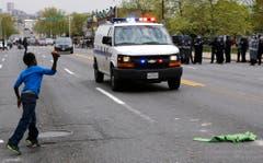 Ein Junge wirft einen Stein in Richtung Polizeitransporter. (Bild: AP Photo/Patrick Semansky)