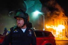 Ein Polizeioffizier vor einem brennenden Haus in der Kravallnacht. (Bild: Keystone/EPA/Noah Scialom)