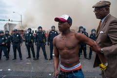 Ein junger Demonstrant wird von einem älteren Herrn zurückgehalten. (Bild: Keystone/EPA/Noah Scialom)