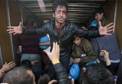 Ein verletzter Mann spricht mit der Menschenmenge, die sich in Idomeni vor einem Lastwagen mit Hilfsgütern versammelt hat. (Bild: Keystone)