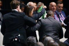 Eine der beiden Frauen wird von Sicherheitskräften weggeführt. (Bild: EPA/WALTER BIERI)