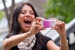 Eine Frau fotografiert sich am Internationalen Tag des Lachens. (Bild: Keystone)