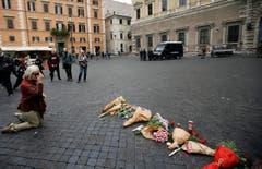 Eine Frau kniet vor Blumen bei der französischen Botschaft in Rom (AP Photo/Gregorio Borgia) (Bild: AP/Gregorio Borgia)