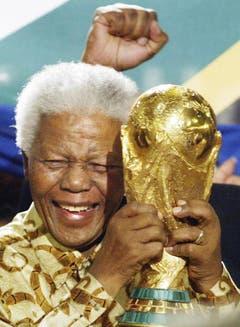 Nelson Mandela hält im May 2004 in Zürich den Fussball Weltpokal in die Höhe, als Südafrika die WM 2010 zugesprochzen erhielt. (Bild: Keystone)
