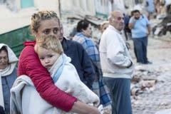 Eine Mutter hält ihren Sohn fest in den Armen. (Bild: EPA / Massimo Percossi)